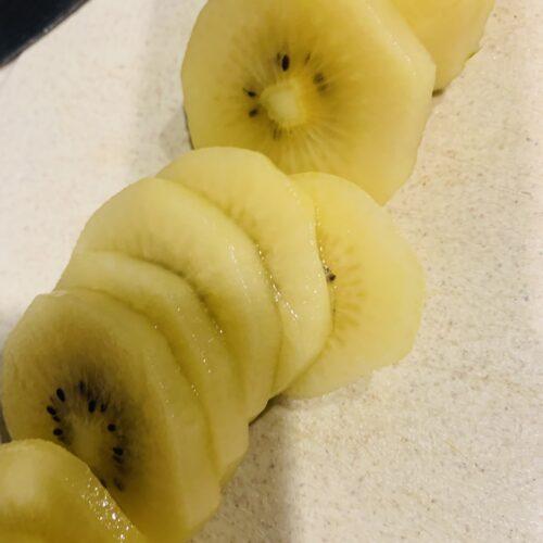 キウイフルーツは皮をむき、1個あたり10枚くらいににスライスする。