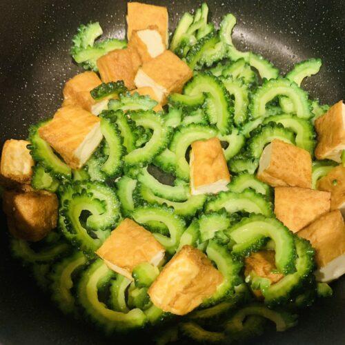 2. フライパンにごま油を入れて熱し、おろしにんにくを入れて中火で香りが出たら  厚揚げを入れて中火で色付くまで炒め、ゴーヤを入れる。